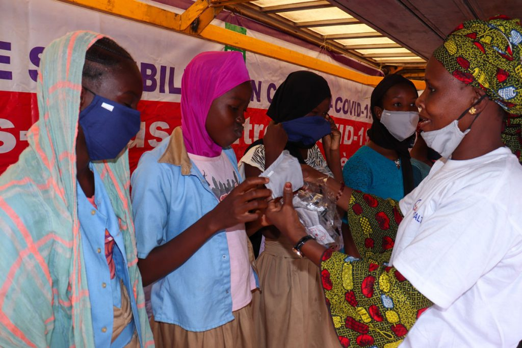 Students demonstrate how to wear new masks at Samè COVID-19 caravan